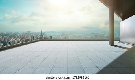 Blickwinkel auf leere Betonfliesen auf der Dachterrasse mit Skyline der Stadt, Morgenszene