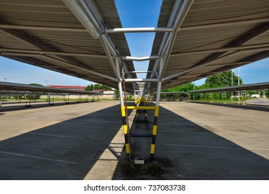 Perspective view of empty outdoor parking lot and metal sheet roof, metal structure with shadow and blue sky background