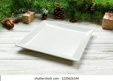 Perspective view. Empty white square plate on wooden christmas background. holiday dinner dish concept with new year decor.