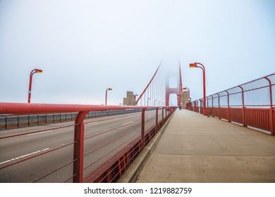 Perspective view of Golden Gate pedestrian path crossing Golden Gate Bridge from Presidio Pacific point to the north. In the fog of San Francisco Californian summer in United States of America.