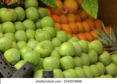 Perspective view of a Granny Smith Apples and  on a street grocery counter in old town. Grapefruit also shown on a minor portion.