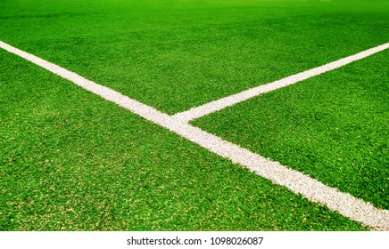Perspective view of green football field with white lines