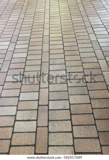 Perspective view of grey pathway paved with brick stones. Ground for sidewalk, pavers - vintage design floor. For background and texture. Portrait orientation.