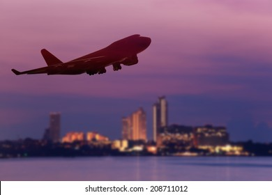 perspective view of jet airliner in flight with city background , use for air transport ,journey and travel industry business