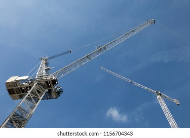 a perspective view looking up at two tall white construction cranes on a building site against a blue sky with clouds