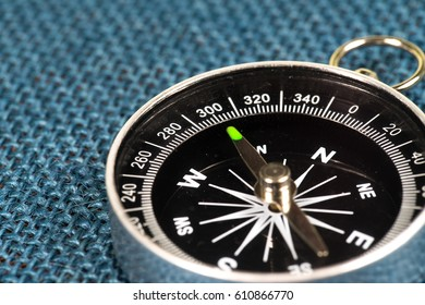 Perspective view of Magnetic Compass on blue sackcloth background.
