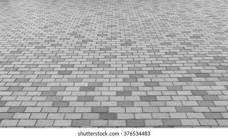 Perspective View Monotone Gray Brick Stone Pavement on The Ground for Street Road. Sidewalk, Driveway, Pavers, Pavement in Vintage Design Ground Flooring Square Pattern Texture Background for mock up
