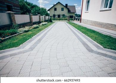 Perspective View of Monotone Gray Brick Stone on The Ground for Street Road. Sidewalk, Driveway, Pavers, Pavement in Vintage Design Flooring Square Pattern Texture Background, house, grass
