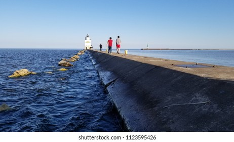 Perspective view of the north pier leading out to the Manitowoc lighthouse on Great Lake Michigan. White granite stones, south pier beacon, pedestrian traffic and choppy water under a clear blue sky.