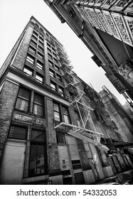 Perspective view of NYC building exterior with fire escape, Black and white.