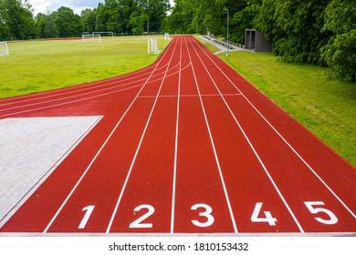 Aussicht auf ein Freiluftstadion mit roten nummerierten Laufstrecken, Infrastruktur für sportliche Aktivitäten