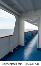 Perspective view of outdoor steel deck at a cruise ship with sea and horizon in the background. Vertical view.