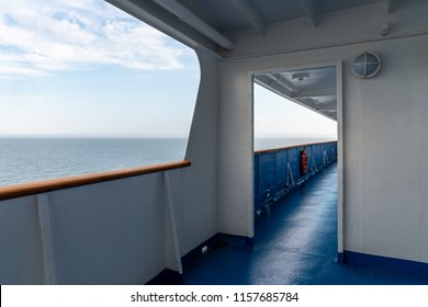 Perspective view of outdoor steel deck at a cruise ship with sea and horizon in the background. Horizontal view.