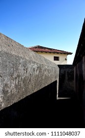 Perspective view of pathway among gray textured wall of Matachin fort on coast of Baracoa city, Cuba