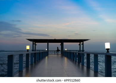 Perspective view of a pier on the sea at sunset with Silhouette of a woman