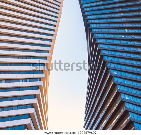 Perspective view of the sky between the twin glass buildings. Sunshine reflection on the glass walls against the blue sky. Close up of black and white similar, modern twisted skyscrapers.