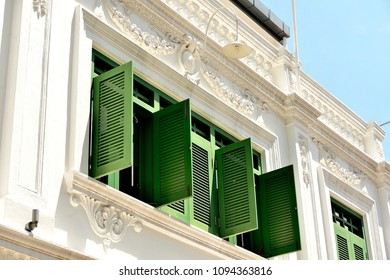 Perspective view of vintage traditional Singapore Peranakan or Straits Chinese shop house exterior with antique green wooden shutters in historic Chinatown.