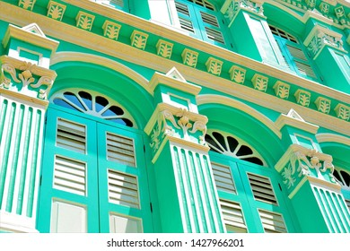 Perspective view of vintage traditional Singapore Peranakan or Straits Chinese shop house with antique green wooden louvered shutters in historic Chinatown in horizontal view