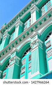 Perspective view of vintage traditional Singapore Peranakan or Straits Chinese shop house with antique green wooden louvered shutters in historic Chinatown in portrait view
