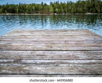Perspective view of a wooden pier with lake and forest in background