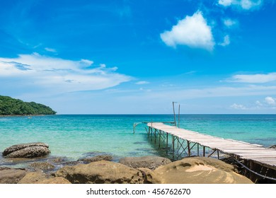 Perspective view of a wooden pier on the ocean of Thailand with clear blue sky and sea