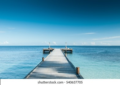 Perspective view of a wooden pier on the tropical seashore with clear blue sky with some white clouds and sea with turquoise water.