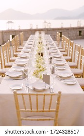 Perspective Wedding dinner table reception view. A long rectangular table with a cream tablecloth and orchid flowers in the center. Against backdrop of mountains, sea and sunset sky