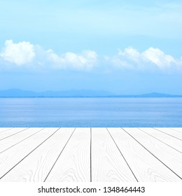 Perspective white wood background,  Wood table over blur perspective blue sea and sky in summer background, White wooden desk, table top surface and sea for summer vacation product display backdrop
