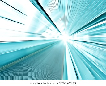 Perspective wide angle view of modern light blue illuminated and spacious high-speed and technology moving escalator with fast blurred trail of handrail in vanishing traffic motion