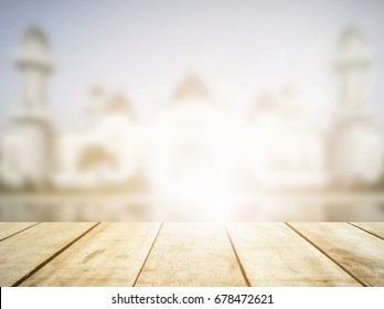 Perspective wood floor on blur mosque ramadan background. Window breakfast table top view bokeh in eid mubarak concept for montage presentation in fasting festival, culture of muslim religious.