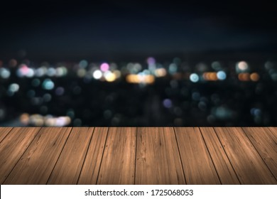 Perspective wooden empty with abstract blurred lights of the city background in the night