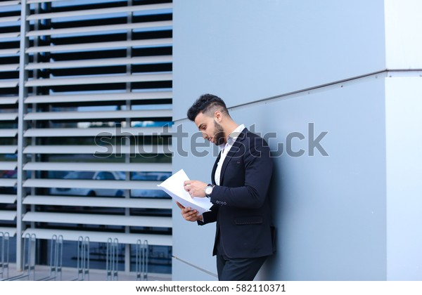 Perspective young adult businessman virile asian guy holds and looks, considers, reads and sorts out papers or documents, stands near gray wall of business center. Bearded man dressed in classic suit