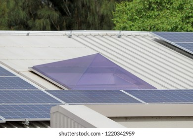 Perspex pyramid shaped skylight on metal roof with solar panels