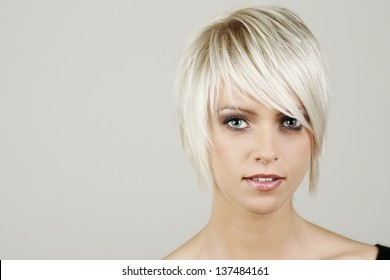 Pert sexy young woman with trendy short blonde hair looking at the camera with parted lips alongside blank copyspace