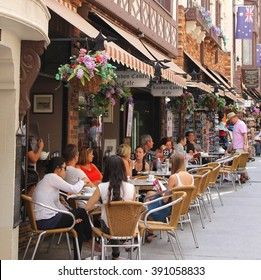 PERTH, AUSTRALIA - April 6. Families and friends enjoy drinks at an outdoor cafe terrace in London Court, an old town street with historical buildings and Australian flag on April 6, 2016 in Perth.