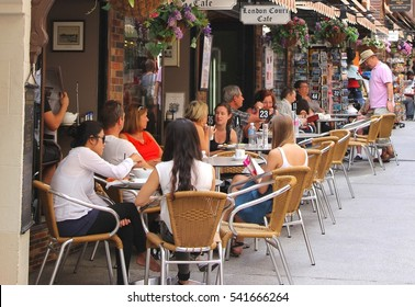PERTH, AUSTRALIA - April 6. Families and friends from different cultures talk, eat and drink at outdoor cafe terrace in London Court, old town street with historic buildings on April 6,2016 in Perth.