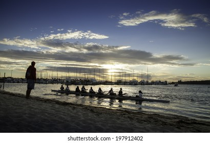 PERTH, AUSTRALIA - FEBRUARY 22, 2014: A coach overseas a schoolgirl rowing crew as they set off for an early morning training session from the beach of Royal Freshwater Bay in Peppermint Grove, Perth.