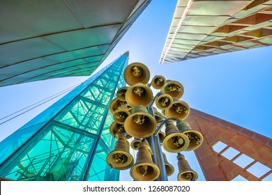 Perth, Australia - Jan 3, 2018: bottom view of copper and glass Bells Tower and tall skyscrapers of Elisabeth Quay in the blue sky. Architecture background. Details bells inside of Swan Bell Tower