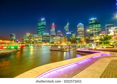 Perth, Australia - Jan 5, 2018: walkway with night lighting at Elizabeth Quay marina and buildings of Central business district reflecting on Swan River, Perth Downtown, Western Australia. Night scene