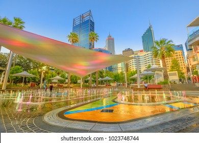 Perth, Australia - Jan 6, 2018: amusing water jets, misting, lighting of a new attraction for kids of BHP Billiton Water Park in Elizabeth Quay. Central business district on background at sunset.