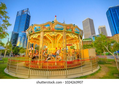 Perth, Australia - Jan 6, 2018: traditional Venetian Carousel at Elizabeth Quay, Perth, WA. Esplanade with modern skyscrapers of Central Business District on background. Blue hour shot. Urban scene.