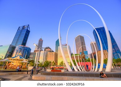 Perth, Australia - Jan 6, 2018: famous landmark in Perth Downtown: Esplanade, skyscrapers of Central Business District, Elizabeth Quay Carousel and Spanda Sculpture in Elizabeth Quay. Sunset light.