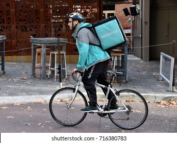 Perth, Australia - May 30, 2017: A Deliveroo rider cycles on a city centre street.