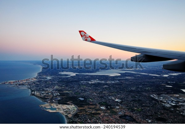 PERTH, AUSTRALIA  NOV 2 2010: AirAsia plane's wing with AirAsia logo, the plane flying over Perth skyline on November 2 2010. World Travel Award 2014 named AirAsia as Asia's Leading Low Cost Airline.