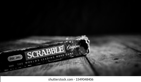 Perth, Scotland - 31 October 2019: Scrabble Board Game   Old Scrabble Box on Vintage Wooden Table   Black and White