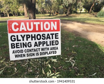 PERTH, WA - MAR 23 2021:Cation Glyphosate being applied. Outdoor sign on city park path. It is used to kill weeds, especially annual broadleaf weeds and grasses that compete with crops.