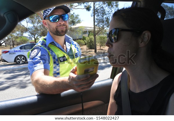 PERTH, WA - OCT 27 2019:Australian traffic police officer using breathalyzer on woman driver during field sobriety testing.Traffic accidents are predominantly caused by Impaired driving