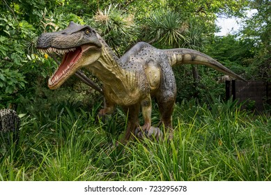 Perth, Western Australia, March 2016: Roaring Baryonyx standing in tall grass display model in Perth Zoo as part of Zoorassic exhibition