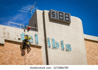 Perth, Western Australia - November 13th 2012:  Workmen removing hotel sign from the outside of building one in harness hanging off side of building