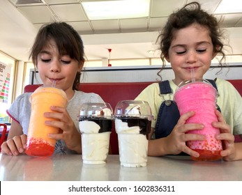 PERTH,WA - JAN 01 2020:Two young girls (Talya and Naomi Ben-Ari age 9-5) drinking Bursties Frozen Drinks.High consumption of high sugar drinks can lead to weight gain, heart disease and diabetes.
